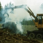 Ernie Leiske and his log loader to pile stumps for burning.